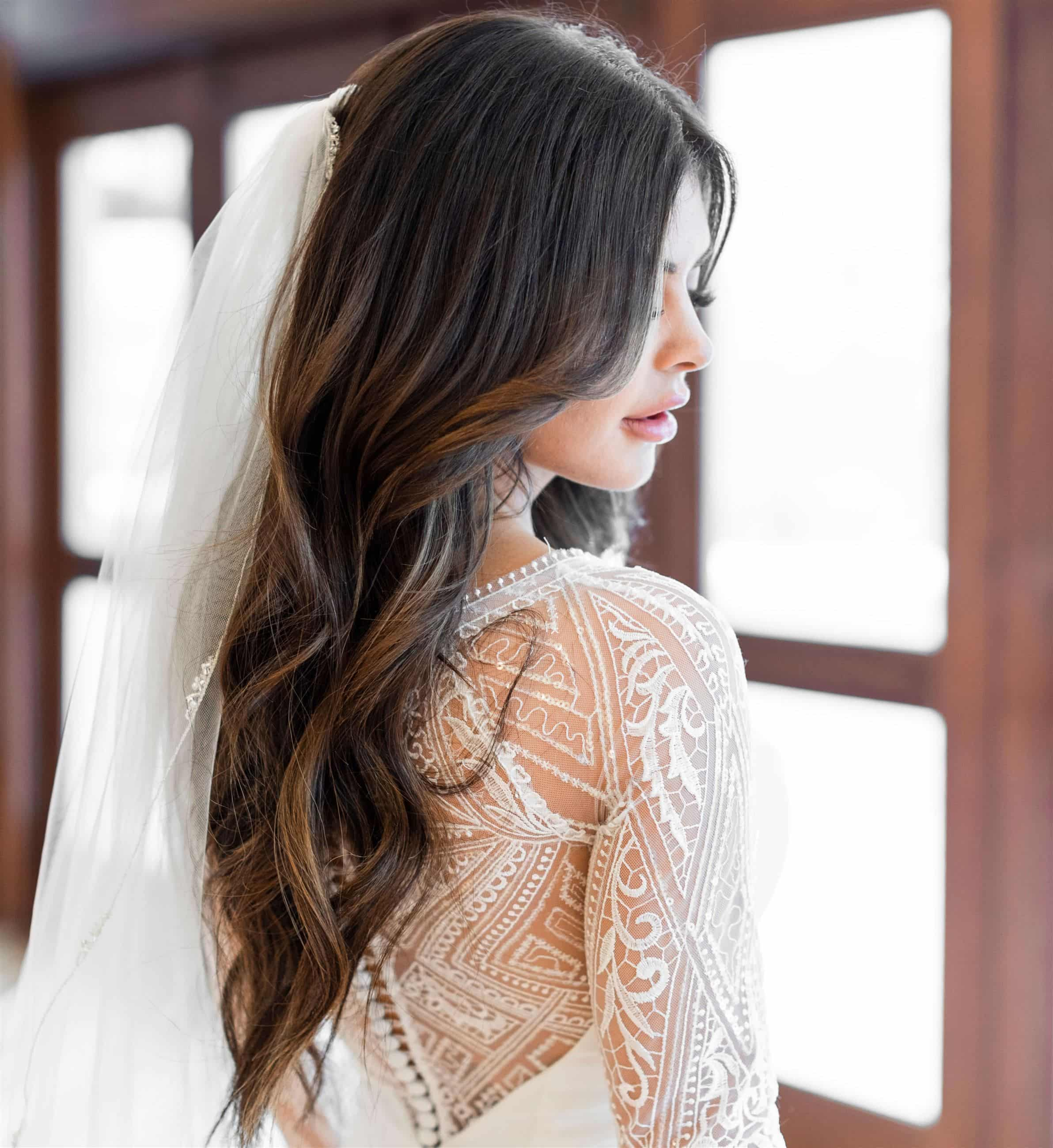 Bride in white long sleeved bridal dress with veil