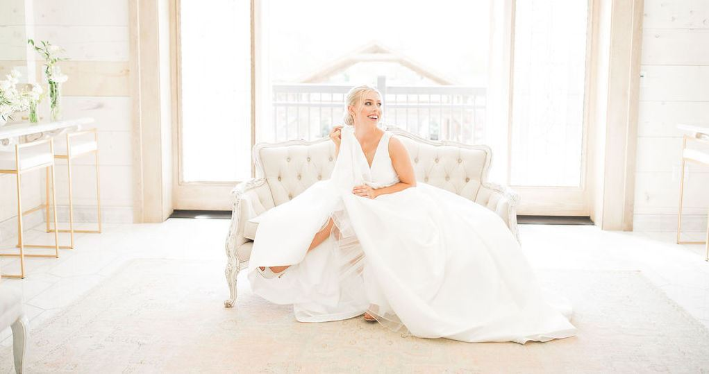 Bride in white wedding dress on couch