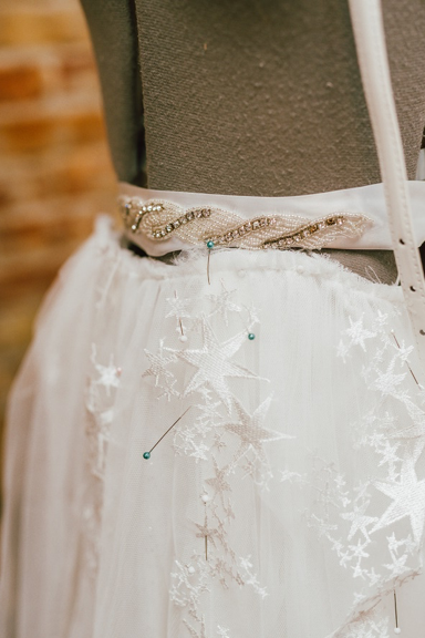 White fabric with star embellishments and beaded belt